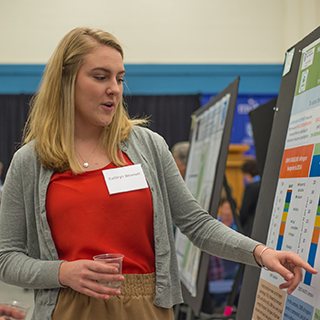 Student pointing at her poster at the Undergraduate Research Conference