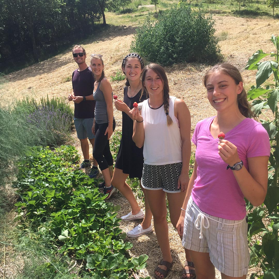 Students in a garden holding up strawberries