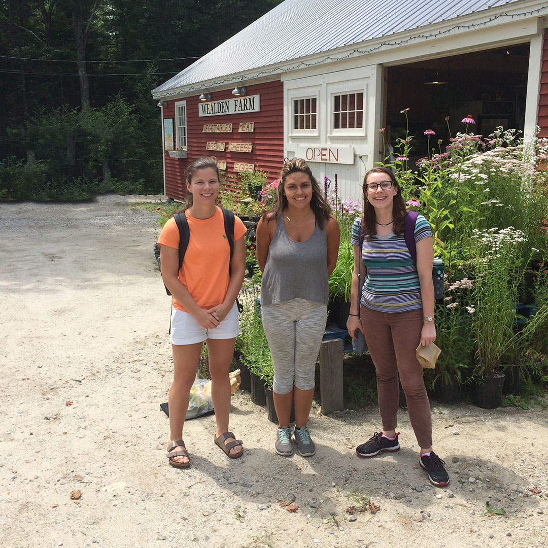 Students standing in front of a barn
