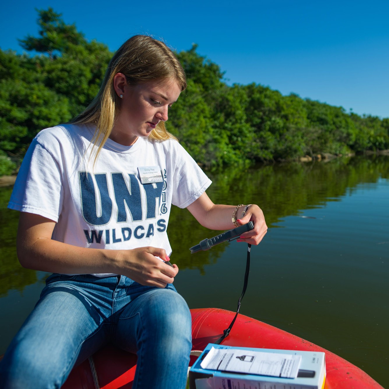 Student taking measurements of lake water