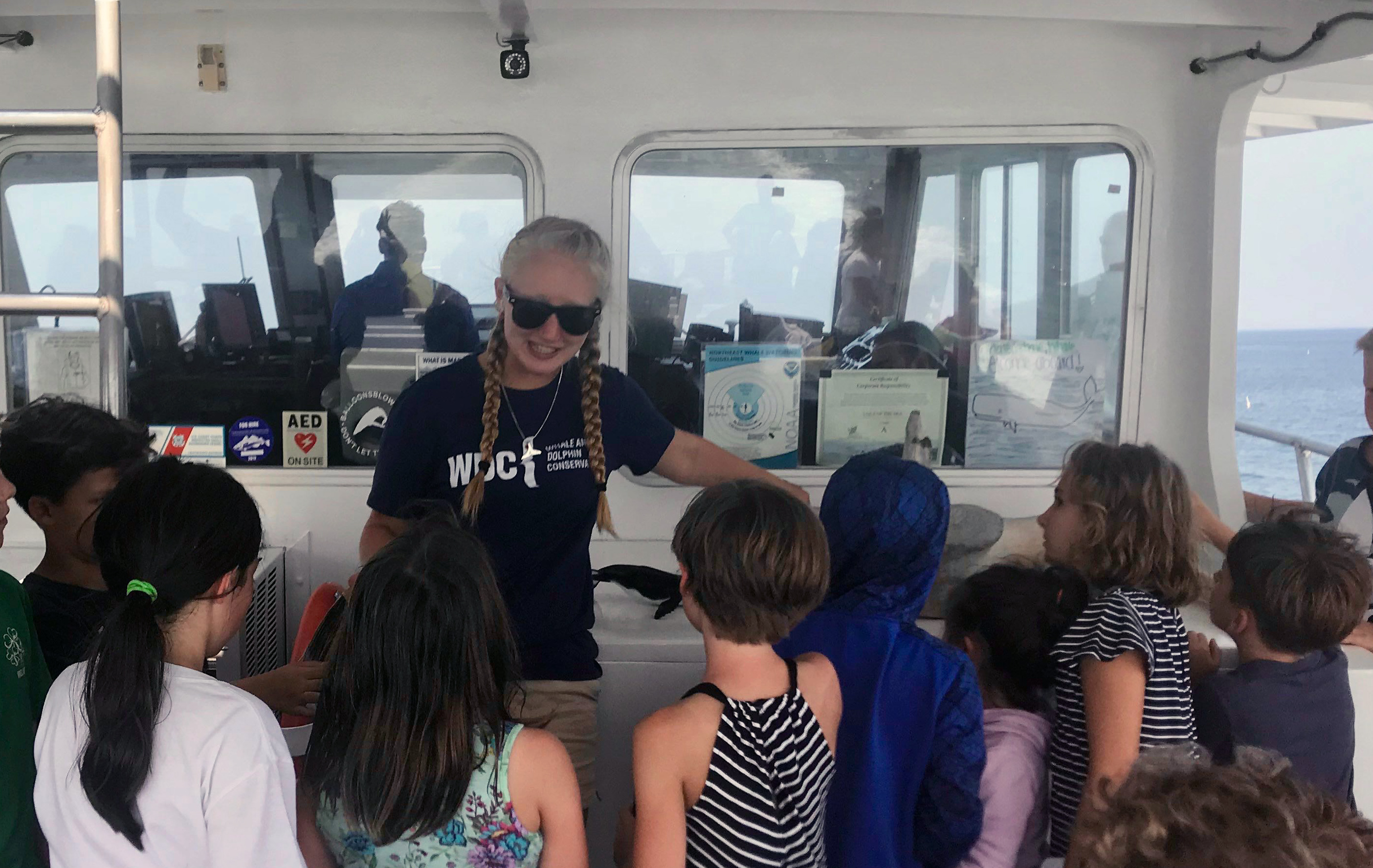 UNH marine, estuarine and freshwater biology major Marissa Cartee '21 talks to children during a whale watch