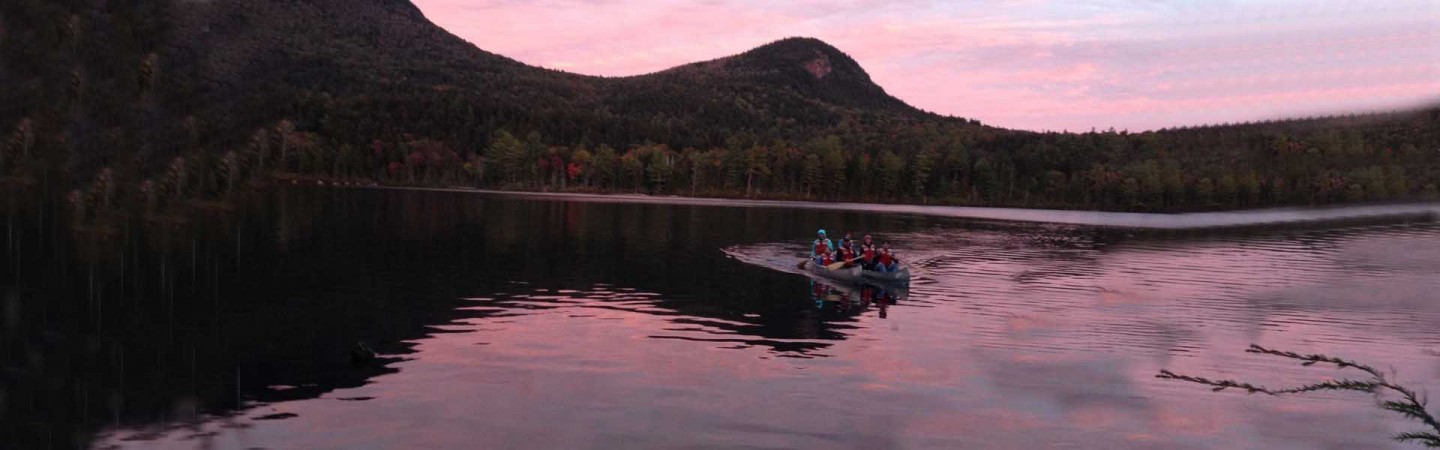 Zoology class in canoes on a lake near sunset