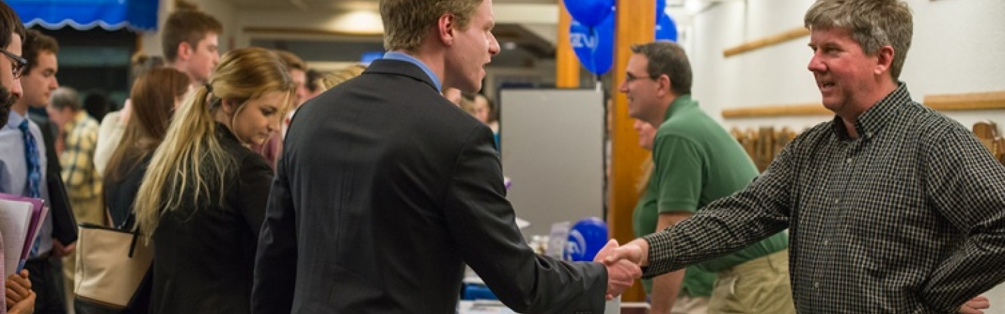 Student shaking hands with a vendor at a career fair