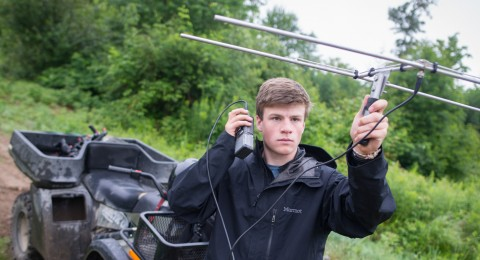 Student holding radio telemetry antenna for wildlife research.