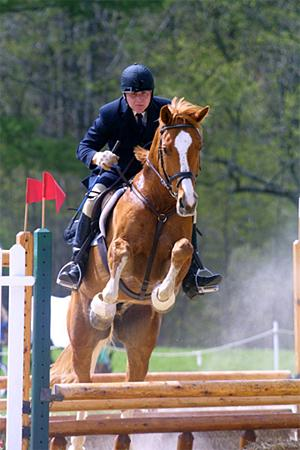 student on horse jumping over bar