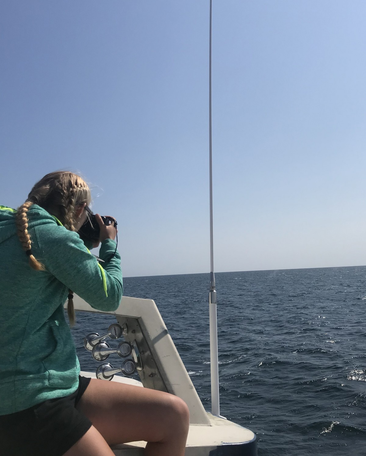 UNH marine, estuarine and freshwater biology major Marissa Cartee photographing whales in the Gulf of Maine